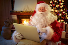 Santa Claus sitting by the fireplace with laptop Royalty Free Stock Images