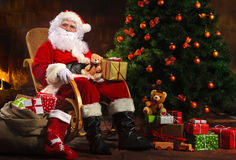 Santa Claus sitting in front of fireplace stock images