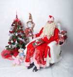 Santa Claus sitting with gifts at the Christmas tree. on a white background.  Stock Images