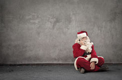 Santa Claus sitting on the ground. Doing a phone call stock image