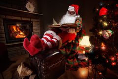 Santa Claus. Sitting at his room at home near Christmas tree and resting by his fireplace stock photography