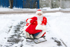 Santa Claus sitting in his sleigh on a city street during the Christmas holiday.  Royalty Free Stock Photo
