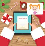 Santa claus is sitting at his workplace desk and receiving letter on his tablet from young girl vector illustration