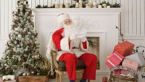 Santa Claus sitting in his workshop reading a letter.  Stock Photography