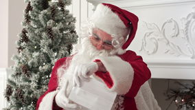 Santa Claus sitting in his workshop reading a letter stock footage