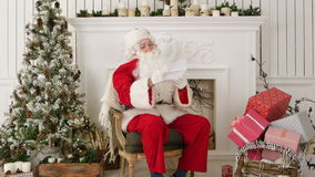 Santa Claus sitting in his workshop reading a letter stock video footage