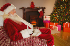 Santa claus sitting and holding his belly Stock Photos