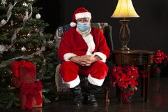 Free Santa Claus Sitting In A Chair Wearing A Surgical Mask And Looking Towards The Camera Stock Images - 193880184