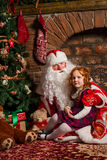 Santa Claus sitting with a little girl. Fireplace and Christmas tree in the background Royalty Free Stock Image