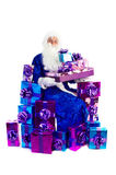 Santa Claus sitting with lots of presents Royalty Free Stock Photo