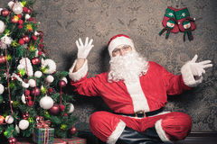 Santa Claus sitting near Christmas tree at eve night Stock Image