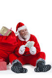Santa claus sitting next to gift counting a currency note Stock Images