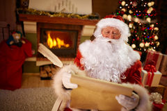 Santa Claus sitting and reading children wishes for Christmas Royalty Free Stock Photo