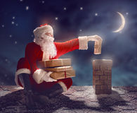 Santa Claus sitting on the roof. Merry Christmas and happy holidays! Santa Claus sitting on the roof of the house and puts the presents in the chimney. Christmas royalty free stock images