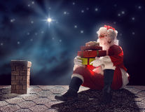 Santa Claus sitting on the roof. Merry Christmas and happy holidays! Santa Claus sitting on the roof of the house and puts the presents in the chimney. Christmas royalty free stock photography