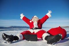Santa Claus sitting on snow glad news in the lapto Stock Photo