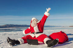 Santa Claus sitting on snow glad news in the laptop Stock Image