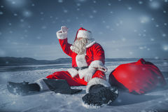Santa Claus sitting in the snow with a laptop and looking away Royalty Free Stock Photos