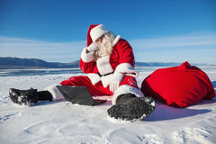 Santa Claus sitting on snow, looking at laptop new Royalty Free Stock Image