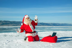 Santa Claus sitting on snow, looking at laptop news Royalty Free Stock Photos