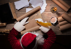 Santa Claus sitting at the table in his room and writing Christmas letter or wish list. Santa Claus sitting at his room and writing Christmas letter or wish list Stock Image