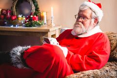 Santa claus sitting and using mobile phone stock images