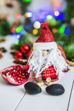 Santa Claus sitting on a white wooden table on a background of green garlands and Christmas lights Stock Photography