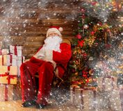 Santa Claus sitting  in wooden home interior Stock Photos
