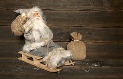 Santa Claus sitzt auf einem hölzernen Pferdeschlitten mit einer Tasche von Geschenken hinter h Lizenzfreies Stockfoto