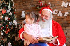 Santa Claus sitzt auf Lehnsessel und liest Buch mit Märchen FO lizenzfreie stockfotografie