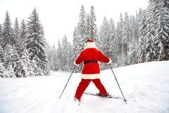 Santa Claus-skiër met skis in het hout in de winter bij Kerstmis stock afbeelding