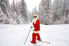 Santa Claus-skiër met skis in het hout in de winter bij Kerstmis stock afbeeldingen