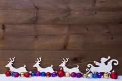 Santa Claus Sled With Reindeer, neige, boules colorées de Noël Images stock