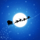 Santa Claus on Sledge. With Reindeer are running across white Moon Royalty Free Stock Images