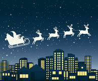 Santa Claus on sledge flies over a city at night. Royalty Free Stock Photo