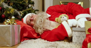 Santa claus sleeping with christmas gifts and teddy bear stock video footage