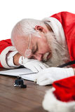 Santa claus sleeping at desk while writing a letter with a quill. During christmas time Royalty Free Stock Photos