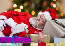 Santa claus sleeping on gift boxes. Tired Santa claus sleeping on gift boxes Stock Images