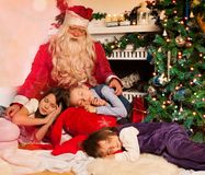 Santa Claus and sleeping kids Stock Photo