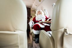 Santa Claus Sleeping In Private Jet. Full length of Santa Claus sleeping in private jet Royalty Free Stock Photography