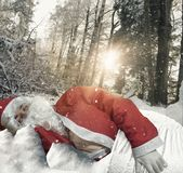Santa claus sleeping in forest environment covered with snow Royalty Free Stock Images