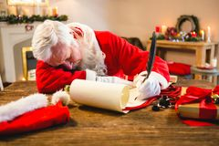 Santa claus sleeping at table while writing a letter with a quill. During christmas time Stock Photo
