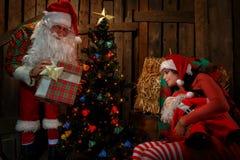 Santa Claus with sleeping woman Stock Photos