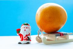 Santa Claus with a sleigh and an orange on a light blue background, Christmas mood royalty free stock images