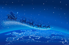 Santa Claus Sleigh Reindeer Blue Stars. Santa Claus in his sleigh with reindeer flying in a dark blue sky over the world Stock Photo