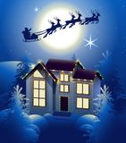 Santa Claus in sleigh reindeer silhouette in background of full moon in night sky. Christmas house illumination in winter forest Stock Photo