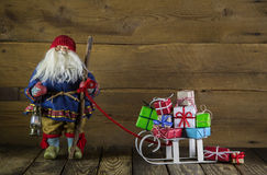 Santa Claus with slide of presents on wooden background for chri Stock Photo