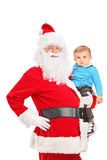 Santa Claus and small child posing. Isolated on white background Stock Photo