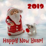 Santa Claus with a small pig - a symbol of 2019 with a congratulatory inscription royalty free stock images