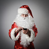 Santa Claus and smart phone. Santa Claus is using a mobile phone royalty free stock images